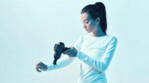 Joven atleta masajeando la mano por la pistola de masaje de mano en la luz de neón, las rutinas de recuperación post-entrenamiento